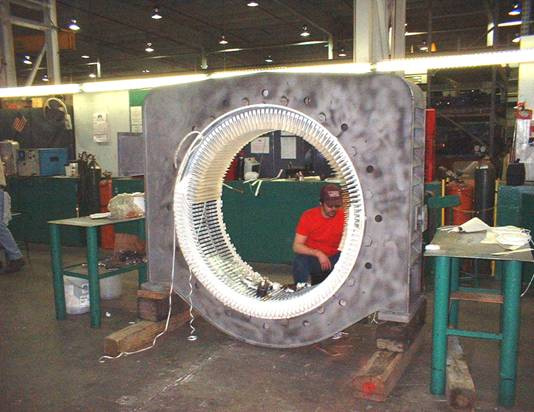 Winding technician installs coils in a 1,500 HP synchronous motor.
